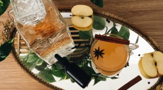 A decanter of bourbon sits on a platter with a bottle of tincture, apples, cloves, and a glass of cider decorated with a cinnamon stick. Chron Vivant